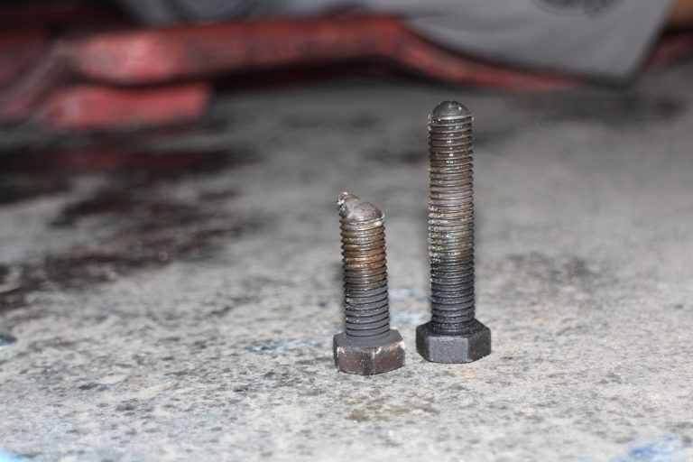 He removed the bolt that adjusts the cam on the end of the driver-side torsion bar and found that it was sheared half its length. He also removed the bolt on the passenger side torsion bar cam for comparison.