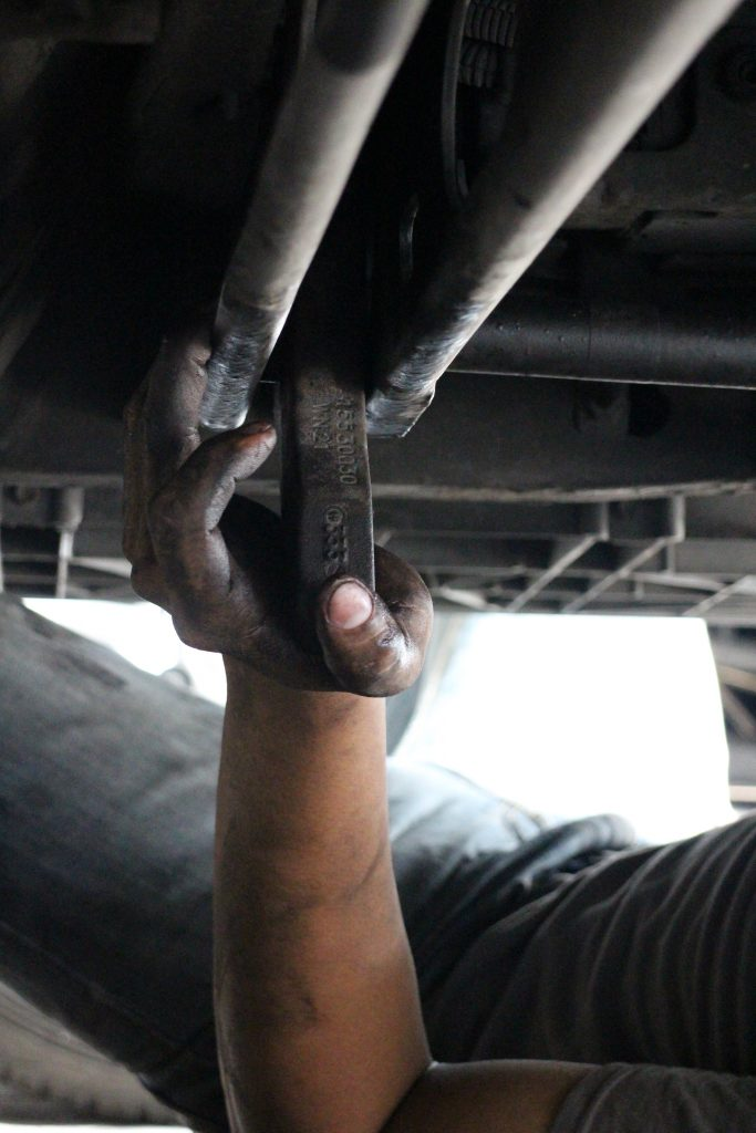 After assessing that the torsion bars were incorrectly adjusted during a previous repair, the mechanic removed the cam stopper and cam to pull the torsion bar.