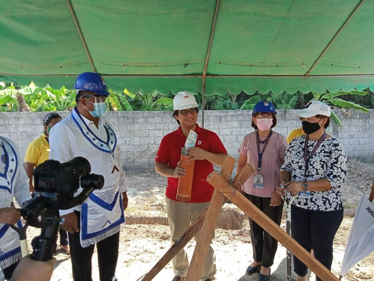 Allan Santos inserts a copy of the Groundbreaking Ceremony Program…