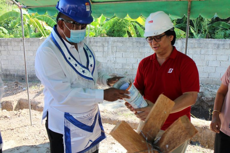 Worshipful Master Ernie Llanillo inserts a copy of the building plans.